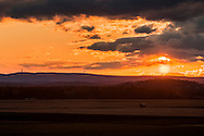Goshen, New York - The sun sets behind Black Dirt farm fields on March 15, 2016. The High Point Monument in New Jersey is in the background at left.