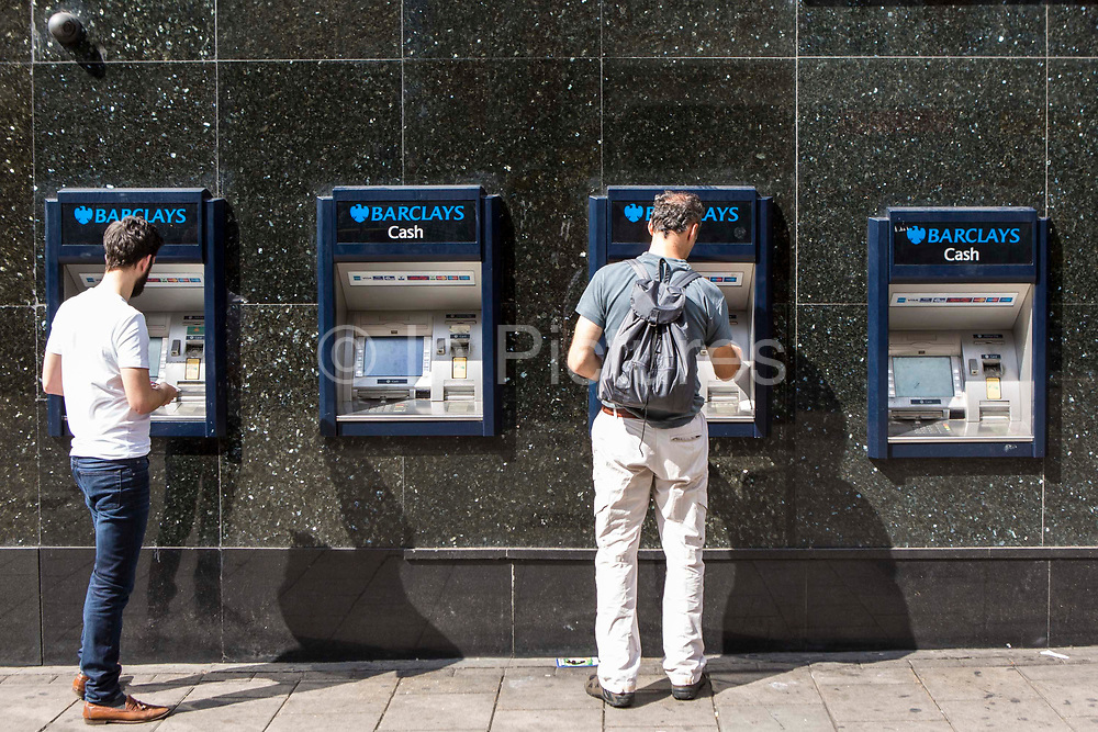 Two men using a Barclays cash machine on a street in London, United Kingdom. These machines are called automated teller machine (ATM) or automated banking machine (ABM).  People are able to access their bank account to withdraw cash, debit card cash advances, check account balances and purchase pre-paid mobile phone credit. Barclays is a British multinational banking and financial services company.