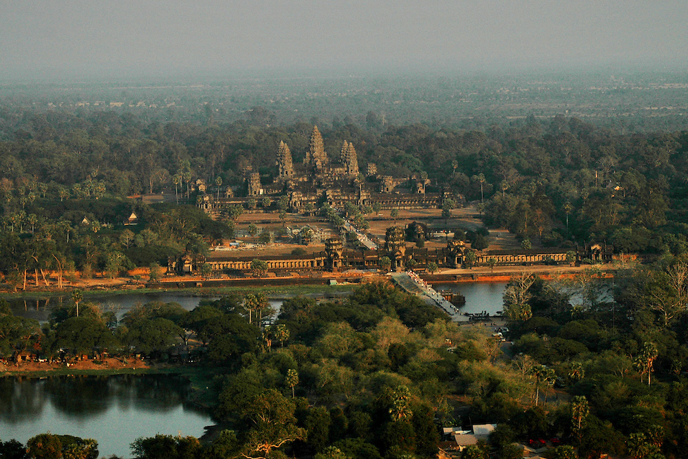 This aerial shot of Angkor Wat, the world's largest single religious monument was shot from a hot air balloon.<br /> <br /> Angkor Wat was built for the king Suryavarman II in the early 12th century as his state temple and capital city.<br /> <br /> It is a massive three-tiered pyramid crowned by five lotus-like towers rising 65 meters from ground level is surrounded by a moat and an exterior wall. All the walls of the temple are covered inside and out with bas-reliefs and carvings. <br /> <br /> The ruins of Angkor, a UNESCO World Heritage Site with temples numbering over 1000, are hidden amongst forests and farmland to the north of the Tonle Sap Lake outside the modern city of Siem Reap, Cambodia. <br />  <br /> It is one of the most awe-inspiring locations I have ever been. From the sunrise to the sunset, there isn't a time of day that is not simply a spectacular time to explore this breathtaking location.