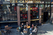 A group of friends enjoy drinks while sitting outside The Cambridge, a typical pub at Cambridge Circus in London's West End, on 12th March 2020, in London, England. The Cambridge was built in 1887 on the site of The King's Arms, next to the Palace Theatre.