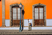An elderly man walks past a colorful colonial style building in the central historic district of Coatepec, Veracruz State, Mexico.