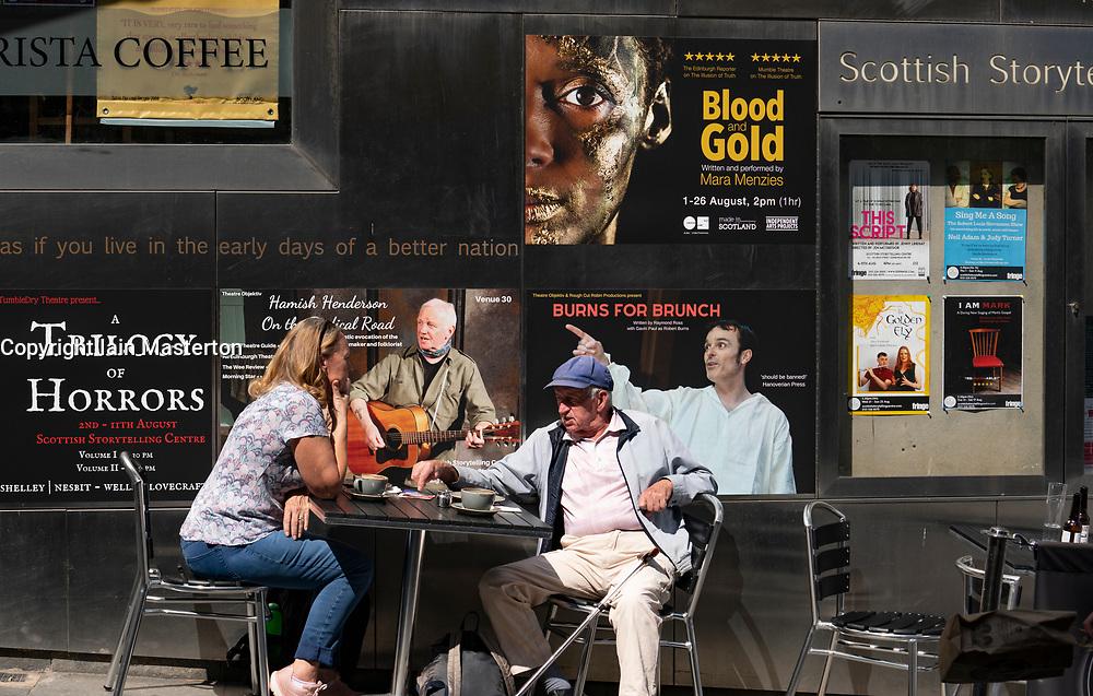 Couple sitting outside the Scottish Storytelling Centre during the Edinburgh Festival on the Royal Mile, Scotland, UK
