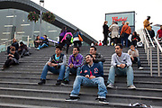 Scene outside as a group of young Asian men sit on the steps on the way to the new Westfield Shoppping Centre in Stratford, East London, UK. This is Europe's largest shopping complex. This is a relatively poor area of London, but in recent years has seen much regeneration, the construction of a major transport hub and various shopping complexes. Stratford is adjacent to the London Olympic Park and is currently experiencing regeneration and expansion linked to the 2012 Summer Olympics.