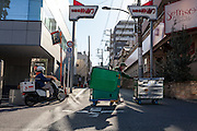 "A worker for Yamato ""Kuroneko"" (Black Cat) delivery company pushes trolleys containing parcels to be delivered in a back street near Waseda in Tokyo. Japan. Thursday January 9th 2015"