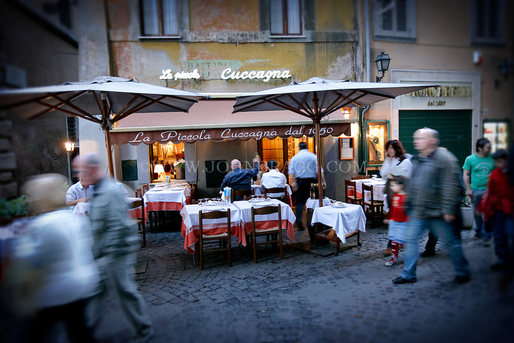 People walking outside of the restaurant La Piccola Cuccagna in Rome, Italy