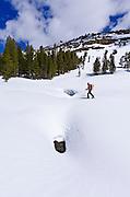 Backcountry skier crossing a snow bridge, Ansel Adams Wilderness, Sierra Nevada Mountains, California USA