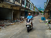 18 JULY 2017 - BANGKOK, THAILAND: A man who used to live on Soi 27 Sathu Pradit leaves his old home after picking up the last of his personal belongings. The area was a working class neighborhood of two storey shophouses. Most of the homes in the were occupied by Thais of Chinese heritage. The owner of the land sold the land to a developer who plans to build a condominium tower on the site. The residents left in early July and the shophouses will be torn down in coming weeks.       PHOTO BY JACK KURTZ