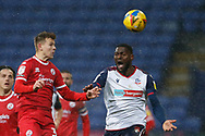 Crawley Town's Jake Hessenthaler heads clear from Bolton Wanderers Ricardo Santos(5) during the EFL Sky Bet League 2 match between Bolton Wanderers and Crawley Town at the University of  Bolton Stadium, Bolton, England on 2 January 2021.