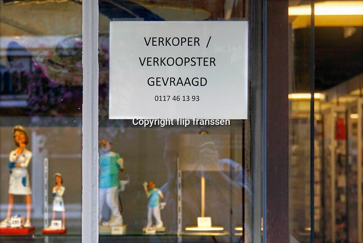 Nederland, Sluis, 13-9-2019Op een winkelruit  is een personeelsadvertentie geplakt . Collega, verkoper, verkoopster, gevraagd, gezocht . Foto: Flip Franssen