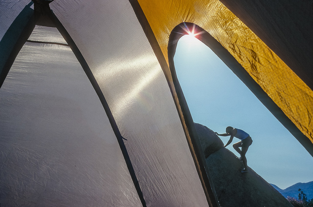 Campers viewed through the opening to a tent, Joshua Tree National Park, California, USA