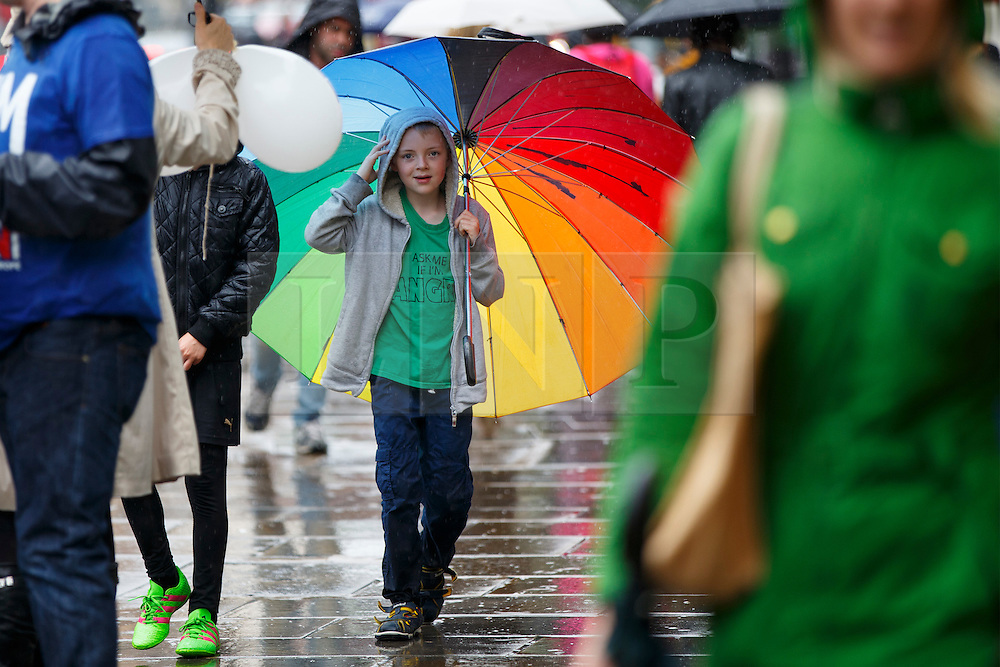 © Licensed to London News Pictures. 23/06/2016. London, UK. A child takes shelter from the rain underneath an umbrella in Islington, London on the polling day of the EU referendum on 23 June 2016. Photo credit: Tolga Akmen/LNP