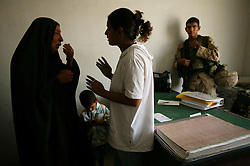 Alyaa Abdul Hassan Abbood, 23, a translator, tries to comfort Beheyen Ibrahim Jar who just found out that her husband died at the hands of a U.S. soldier, Baghdad, Iraq, Sept. 27, 2003. Abbood works with the U.S. military to mediate as Iraqi civilians come in to receive monetary compensation for damages done by American troops in Baghdad.