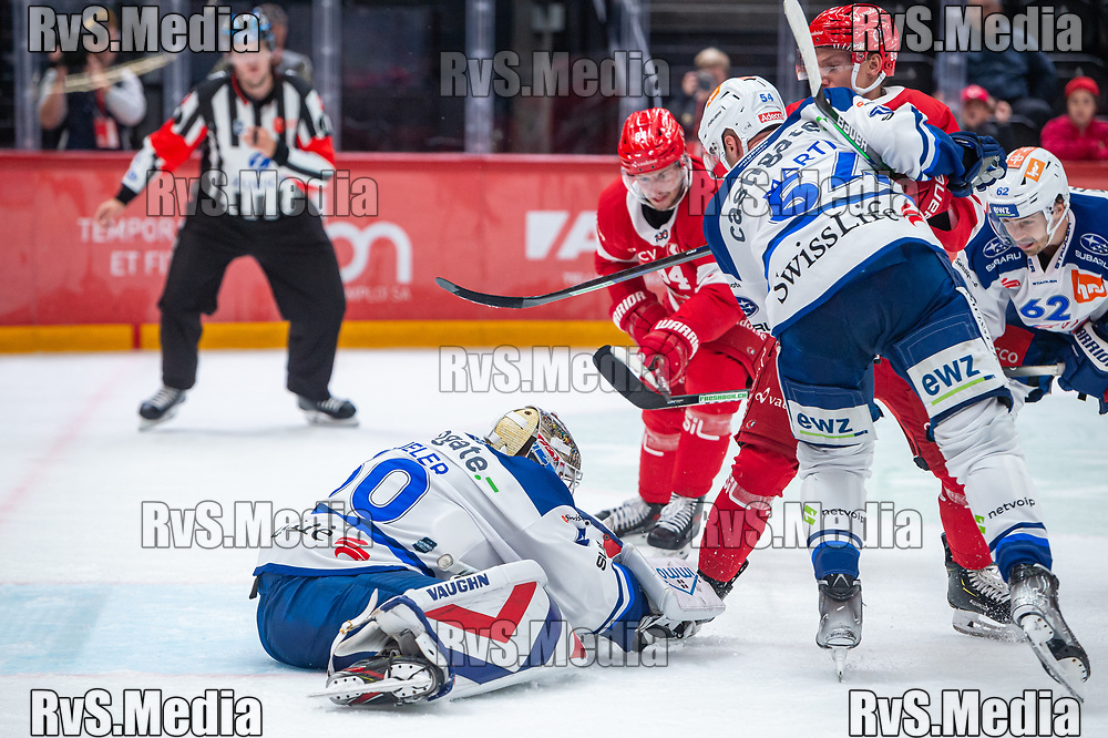 LAUSANNE, SWITZERLAND - OCTOBER 01: Benjamin Baumgartner #98 of Lausanne HC tries to score against Goalie Lukas Flueler #30 of ZSC Lions during the Swiss National League game between Lausanne HC and ZSC Lions at Vaudoise Arena on October 1, 2021 in Lausanne, Switzerland. (Photo by Monika Majer/RvS.Media)