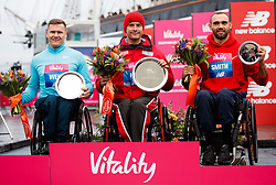 The winner of the men's wheelchair race Marcel Hug (centre) alongside second placed David Weir (left) and third placed Will Smith (right) during the Vitality Big Half in London City Centre.