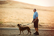 Older man walking dog, looking at hills