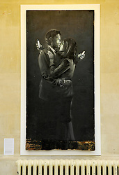 © Licensed to London News Pictures. 18/04/2014; Bristol, UK.  Artwork by Banksy titled 'Mobile Lovers' on display at the City of Bristol Museum and Art Gallery run by Bristol City Council.  The artwork was found earlier this week on a doorway in Clement Street in Bristol by Broad Plain & Riverside Youth Project, whose staff removed it into the boys club for safe keeping and to raise money to help the club survive.  The ownership of the work is in dispute and the work was taken to the city museum pending a decision on its future.<br /> Photo credit: Simon Chapman/LNP
