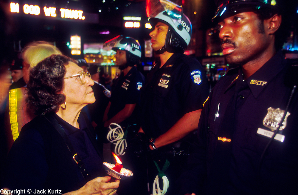NEW YORK, NY: A woman opposed to US military retaliation for the attack on the World Trade Centerconfronts a New York police officer during a demonstration in Times Square in New York, Sept 21, 2001. Terrorists crashed two hijacked jetliners into the World Trade Center collapsing the towers on Sept 11, 2001, killing more 2,900 people. About 500 people marched through New York ending up in Times Square to protest the expected US military retaliation.    PHOTO BY JACK KURTZ