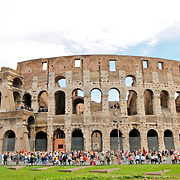 ROME, Italy - At daytime shot of Rome's famous Coliseum, with crowds of tourists milling arounds its base.