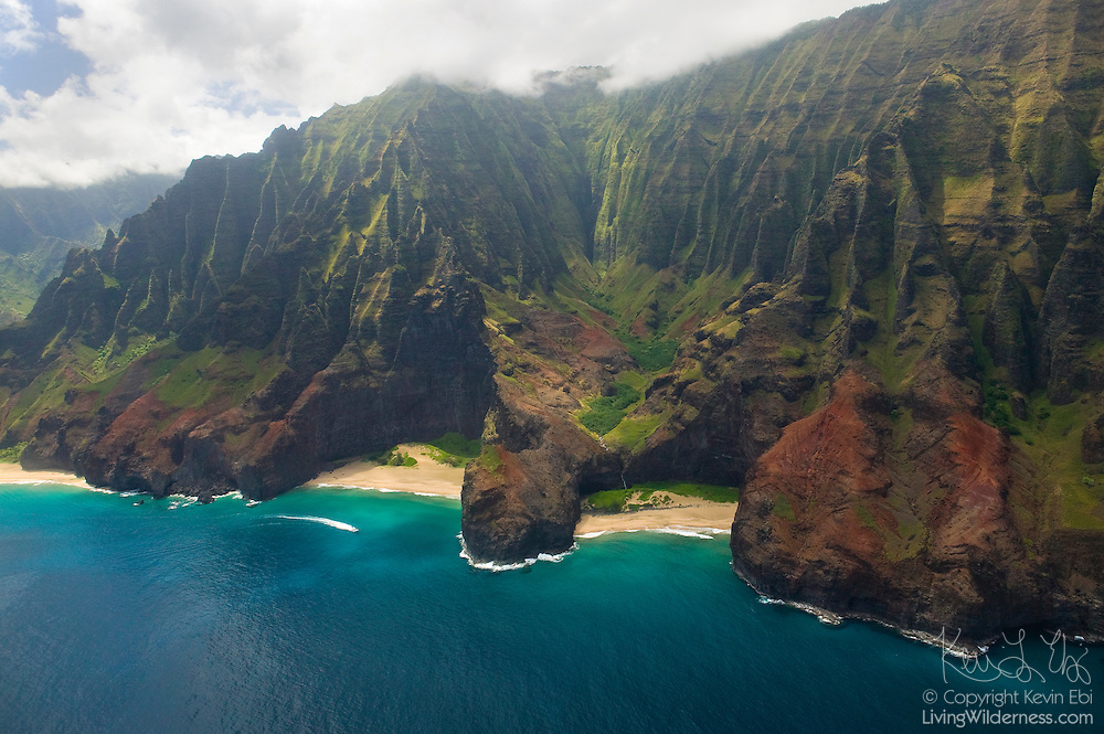 A power boat races between narrow canyons that meet the Pacific Ocean along the Na Pali coast of Kauai, Hawaii.