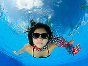 A 12 year old female teen free diving underwater in a swimming pool with a colorful scarf and sunglasses. Model release available