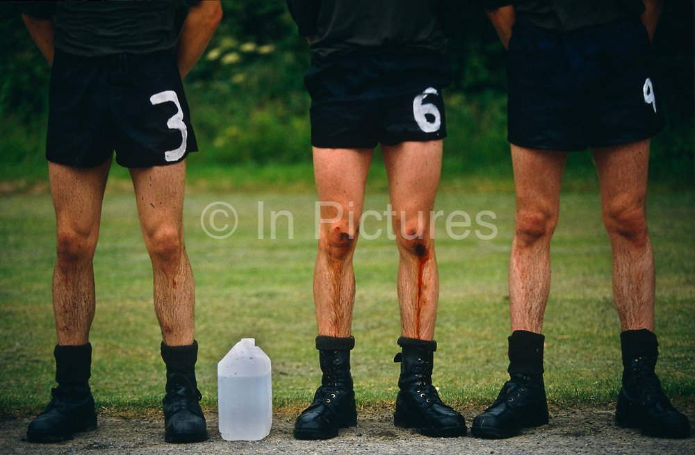 Three soldier recruits wearing shorts and black army boots, one with blood trickling down from the knees to the shins, stand at ease, lined up for inspection after the rigorous steeple-chase endurance race, an individual test with candidates running against the clock over a 1.8 mile cross country course. The course features a number of 'water obstacles' and having completed the cross country element, candidates must negotiate and 'Assault Course' to complete the test. This forms part of  the 14-week long Pegasus (P) Company selection programme. Recruits wanting to join the British Army's Parachute Regiment held regularly at Catterick army barracks, Yorkshire, need to pass this and other tests before earning the right to wear the esteemed maroon beret. A plastic bottle of water stands between recruit number three (3) and six (6).