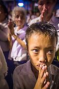 """04 FEBRUARY 2013 - PHNOM PENH, CAMBODIA:  A Cambodian boy prays at the cremation of their former King Norodom Sihanouk during the King-Father's cremation service in Phnom Penh. Norodom Sihanouk (31 October 1922- 15 October 2012) was the King of Cambodia from 1941 to 1955 and again from 1993 to 2004. He was the effective ruler of Cambodia from 1953 to 1970. After his second abdication in 2004, he was given the honorific of """"The King-Father of Cambodia."""" Sihanouk died in Beijing, China, where he was receiving medical care, on Oct. 15, 2012.   PHOTO BY JACK KURTZ"""