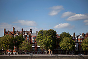 Red brick mansion buildings along Chelsea Embankment. The river Thames flows past this affluent area.