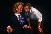 In the year of her being deposed in a leadership challenge is the satirical puppet of Margaret Thatcher with Spitting with Spitting Image co-creator Peter Fluck and wears a blue Conservative rosette and For Hire sticker on 20th March 1992, in London England. Peter Nigel Fluck is a caricaturist and one half of the partnership known as Fluck and Flaw (with Roger Law), creators of the satirical TV puppet show Spitting Image.