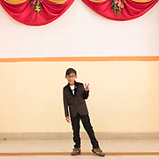 A young child poses, giving the peace sign at a wedding.