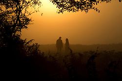 © London News Pictures. 06/10/2013. Richmond, London, UK.  A couple walking at sunrise in autumn at Richmond Park, West London. The UK is experiencing an unusually warm start to the Autumn with temperatures reaching 20 degrees in parts.  Photo credit: Ben Cawthra/LNP