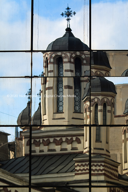 Office windows reflecting the spire of a church on Calea Victoriei in Bucharest, Romania