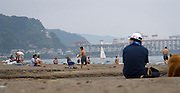 Man and his dog on the beach at Kamakura, Tokyo, Japan. Taken as candid, with the camera sitting on a blanket, letting autofocus make the decision. Editorial Only