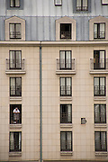 man staring out from his balcony to the street Paris France