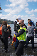 """One million asylum seekers, many of them refugees from Syria, Iraq, and Afghanistan, crossed to Europe by sea in 2015. Half of these came via the Greek island of Lesbos, which is located in the Aegean Sea and has a resident population of about 86,000 people.<br /> <br /> __________<br /> <br /> <br /> Wanting to keep to a tight budget, I did not rent a car like many journalists covering the migrant crisis on Lesbos. I had only one day to work on the island's north coast and gambled that I would be able to hitch a ride from the town where I stayed to the beaches where boats would likely land. It turned out to be not as easy I had hoped, but in time a van of three Norwegians gave me a lift, and many of the pictures I took this day are thanks to their vehicular hospitality.<br /> <br /> They had arrived the night before from Norway, and I asked why they had come. The man who drove the van and is seen carrying the girl in this picture — I no longer remember his name — answered something like this: """"I watch the news like everyone else. You watch it and you see that there is a crisis and then you ask yourself if you can do anything to help. The answer is yes, you can help. Next I called my friends and said we need to respond to this tragedy. Each one agreed. We booked a ticket, took time off work, and here we are."""""""