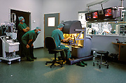 Visiting doctors watch surgeon Volkmar Falk perform a coronary artery bypass graft on a patient lying in the adjoining room, using a tele-manipulated surgical system (called a robotic system by some) designed by Intuitive Surgical Corporation of Mountainview, California, at the Herzzentrum, Leipzig, Germany. The assistant surgeon has incised small holes into the patient's chest wall through which the instruments, attached to sterile plastic covered manipulating arms, will pass and be telemanipulated by the surgeon in the next room. The room in which the surgeon is working is a less sterile work environment than that of the operating room where the patient lies.