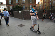 A young man outside OId Street Underground Station looking at his mobile phone whilst riding a scooter on 5th August 2016 in London, United Kingdom. From the series Our Small World, an observation of our mobile phone obsessions