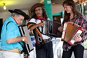 Male Brazilian Gaucho cowboy and female musicians playing accordians and singing. Gaucho cowboy Rodeo, Flores de Cunha, Rio Grande do Sul.