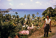 View over corrugated iron roofs of houses to tropical sea, British woman tourist posing, Trinidad and Tobago 1961-1963