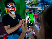 26 AUGUST 2018 - GEORGE TOWN, PENANG, MALAYSIA: A performer is photographed by a child with a smart phone before a Hokkien style Chinese opera on the Lim Jetty in George Town for the Hungry Ghost Festival. The opera troupe came to George Town from Fujian province in China. The Hungry Ghost Festival is a traditional Buddhist and Taoist festival held in Chinese communities throughout Asia. The Ghost Festival, also called Ghost Day, is on the 15th night of the seventh month (25 August in 2018). During the Hungry Ghost Festival, the deceased are believed to visit the living. In many Chinese communities, there are Chinese operas and puppet shows and elaborate banquets are staged to appease the ghosts.     PHOTO BY JACK KURTZ