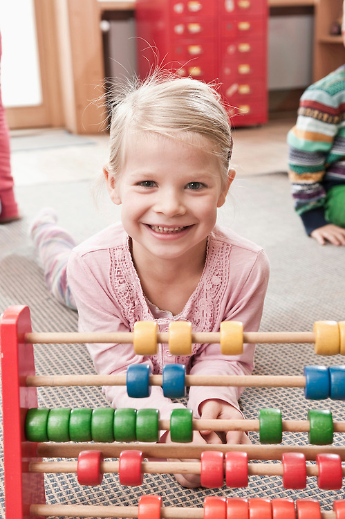 Portrait of little girl playing with wooden slite rule in her kindergarten