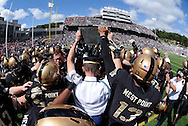 """Army players reach to touch the plaque bearing a quote from General George Marshall on the field prior to their game against Stanford in Michie Stadium at the United States Military Academy in West Point, NY on Saturday, September 14, 2013. The plaque reads, """"I want An Officer For A Secret And Dangerous Mission. I Want A West Point Football Player.""""  Stanford defeated Army 34 - 20."""