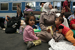 © Gabriel Szabo - Licensed to London News Pictures. Budapest, Hungary. A young family wait at Keleti station in Hungary. Some of the refugees boarded trains which took them to a temporary camp along the train line in Bicske. Photo credit: Gabriel Szabo/LNP
