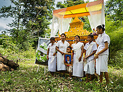 20 JUNE 2016 - DON KHONE, CHAMPASAK, LAOS: Mourners gather in front of the coffin before a man's cremation in the jungle near Don Khone village on Don Khone Island. Don Khone Island, one of the larger islands in the 4,000 Islands chain on the Mekong River in southern Laos. The island has become a backpacker hot spot, there are lots of guest houses and small restaurants on the north end of the island. In the southern Lao funeral tradition, the deceased is cremated at the place of his choosing, usually a place he (or she) was especially fond of. In this case, the man chose to be cremated in a small clearing in the jungle a few kilometers from his home.     PHOTO BY JACK KURTZ