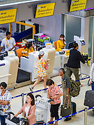 "23 FEBRUARY 2016 - BANGKOK, THAILAND:  Passengers check in for domestic flights on Nok Air in Don Mueang Airport. Nok Air, partly owned by Thai Airways International and one of the largest and most successful budget airlines in Thailand, cancelled 20 flights Tuesday because of a shortage of pilots and announced that other flights would be cancelled or suspended through the weekend. The cancellations came after a wildcat strike by several pilots Sunday night cancelled flights and stranded more than a thousand travelers. The pilot shortage at Nok comes at a time when the Thai aviation industry is facing more scrutiny for maintenance and training of air and ground crews, record keeping, and the condition of Suvarnabhumi Airport, which although less than 10 years old is already over capacity, and facing maintenance issues related to runways and taxiways, some of which have developed cracks. The United States' Federal Aviation Administration late last year downgraded Thailand to a ""category 2"" rating, which means its civil aviation authority is deficient in one or more critical areas or that the country lacks laws and regulations needed to oversee airlines in line with international standards.        PHOTO BY JACK KURTZ"