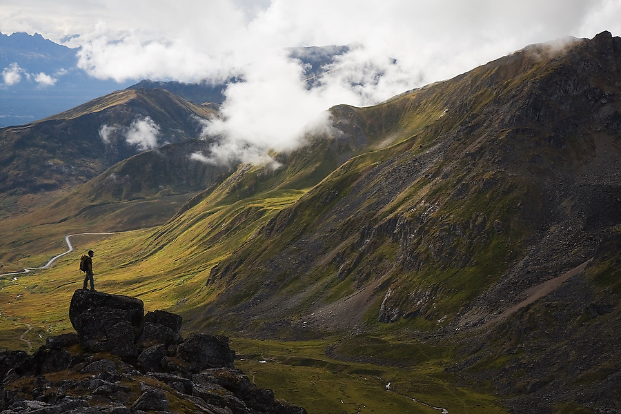 Hiker Craig Weilands stands on a rock outcrop looking down at the Independence Mine State Historical Park in the Talkeetna Mountains near Hatcher Pass, Alaska.