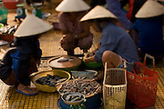 Vietnamese women clean fish in a Hoi An market before selling them.