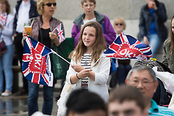 Trafalgar Square, London, June 12th 2016. Rain greets Londoners and visitors to the capital's Trafalgar Square as the Mayor hosts a Patron's Lunch in celebration of The Queen's 90th birthday. PICTURED: A girl waves her flags as hundreds enjoy the atmosphere.
