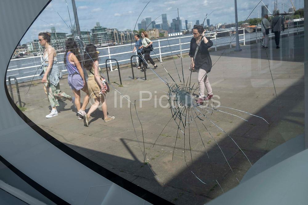 Passers-by walk through sunlight with the impact marks from vandalised glass at Butlers Wharf, on 11th June 2021, in London, England.