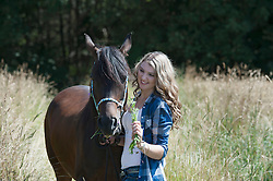 Young woman feeding her brown horse on meadow and smiling, Bavaria, Germany