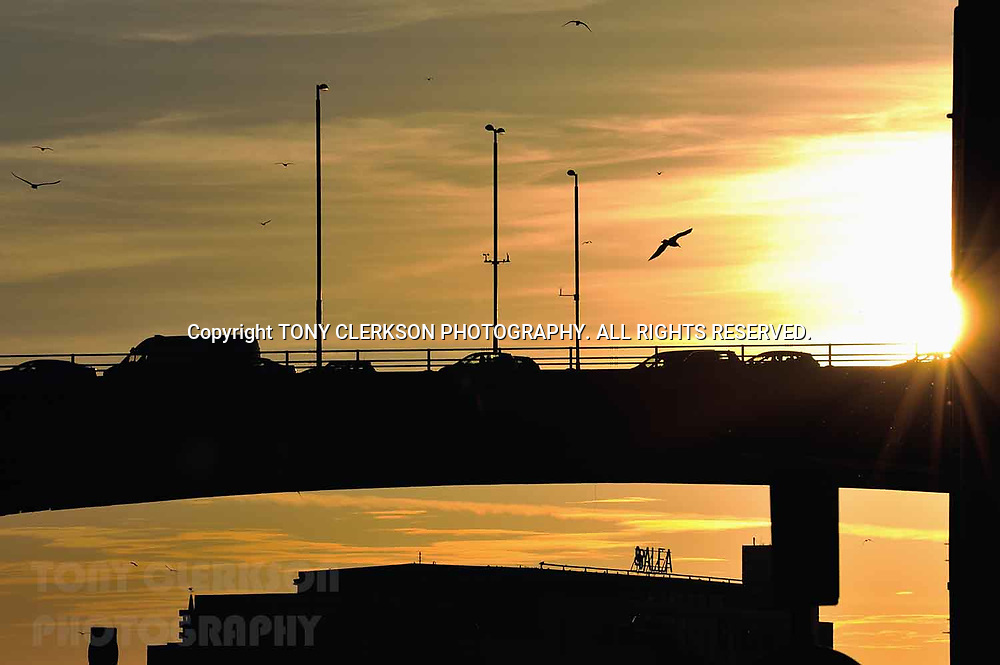 Sunset lights up Glasgow along the River Clyde silhouetting the Kingston Bridge